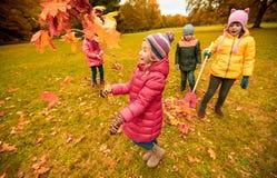 Enfants heureux jouant avec des feuilles d'automne en parc Photo stock
