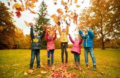 Enfants heureux jouant avec des feuilles d'automne en parc Image stock