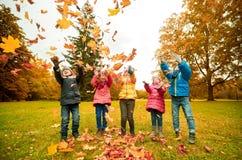 Enfants heureux jouant avec des feuilles d'automne en parc Images stock