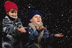 Enfants heureux jouant avec des flocons de neige sur la promenade d'hiver images libres de droits