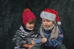 Enfants heureux jouant avec des flocons de neige sur la promenade d'hiver image stock