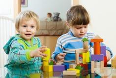 Enfants heureux jouant avec des jouets dans la maison Image stock