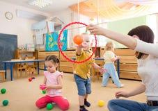 Enfants heureux jouant avec la boule et l'anneau dans le jardin d'enfants Photo libre de droits