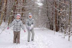 Enfants heureux jouant avec la neige dans la forêt d'hiver, week-end d'hiver de famille Photo stock