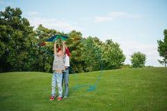 Enfants heureux jouant avec le cerf-volant sur l'herbe verte en parc Photo stock