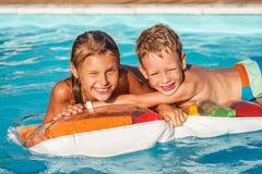 Enfants heureux jouant dans l'eau bleue de la piscine Photographie stock libre de droits