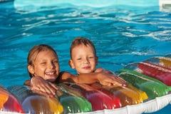 Enfants heureux jouant dans l'eau bleue de la piscine Images libres de droits