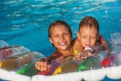 Enfants heureux jouant dans l'eau bleue de la piscine Photo libre de droits
