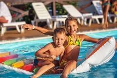 Enfants heureux jouant dans l'eau bleue de la piscine Images stock