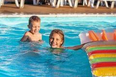 Enfants heureux jouant dans l'eau bleue de la piscine Photos stock