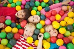 Enfants heureux jouant dans la piscine de boule Photo stock