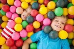 Enfants heureux jouant dans la piscine de boule Image libre de droits