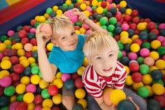 Enfants heureux jouant dans la piscine de boule Photographie stock libre de droits
