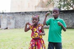 Enfants heureux jouant dehors avec la bulle de savon photos stock
