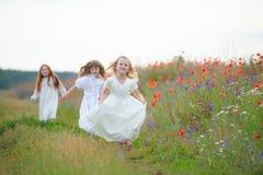 Enfants heureux jouant dehors Exécution de trois jeunes filles Photographie stock libre de droits