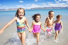 Enfants heureux jouant et éclaboussant dans l'océan Image libre de droits