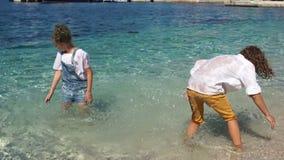 Enfants heureux jouant les uns avec les autres en eau de mer de turquoise, vacances méditerranéennes, vacances d'école banque de vidéos