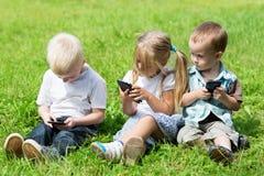 Enfants heureux jouant sur des smartphones Photos stock