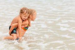 Enfants heureux jouant sur la plage images libres de droits