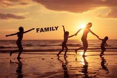 Enfants heureux jouant sur la plage au temps de coucher du soleil Image libre de droits