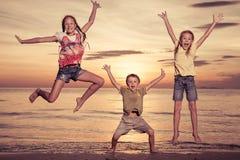 Enfants heureux jouant sur la plage au temps de coucher du soleil Photos libres de droits