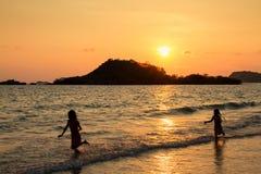 Enfants heureux jouant sur la plage au temps de coucher du soleil Photographie stock