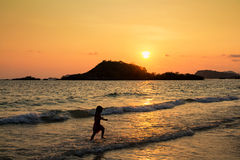 Enfants heureux jouant sur la plage au temps de coucher du soleil Photo stock