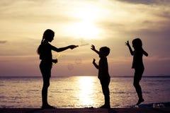 Enfants heureux jouant sur la plage au temps de coucher du soleil Images libres de droits