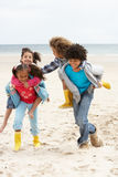Enfants heureux jouant sur le dos sur la plage Photographie stock libre de droits