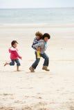 Enfants heureux jouant sur le dos sur la plage Photo libre de droits