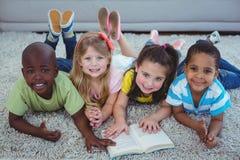 Enfants heureux lisant un livre ensemble Image libre de droits