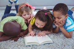 Enfants heureux lisant un livre ensemble Image stock