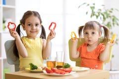 Enfants heureux mangeant de la nourriture saine dans le jardin d'enfants ou à la maison Photos stock