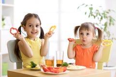 Enfants heureux mangeant de la nourriture saine dans le jardin d'enfants ou à la maison Images stock