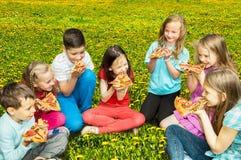 Enfants heureux mangeant de la pizza dehors photo stock