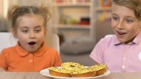 Enfants heureux mangeant des beignets avec grand désir, habitudes malsaines de nutrition banque de vidéos