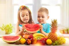 Enfants heureux mangeant la pastèque avec des fruits dans la cuisine Photo stock