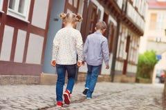 Enfants heureux marchant dans la ville ensoleillée Photo stock