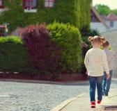 Enfants heureux marchant dans la ville ensoleillée Photos stock