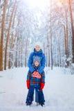Enfants heureux marchant et ayant l'amusement le jour neigeux d'hiver Photo stock