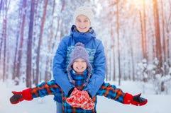 Enfants heureux marchant et ayant l'amusement le jour neigeux d'hiver Images libres de droits