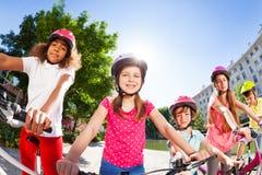 Enfants heureux montant des vélos dans la ville d'été Images stock