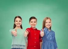 Enfants heureux montrant des pouces au-dessus de conseil vert Images stock