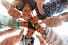 Enfants heureux montrant des pouces dans le cercle Image libre de droits