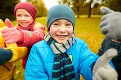 Enfants heureux montrant des pouces dans le parc d'automne Photo libre de droits