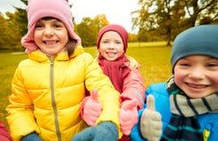Enfants heureux montrant des pouces dans le parc d'automne Photos stock