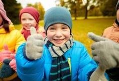 Enfants heureux montrant des pouces dans le parc d'automne Images libres de droits