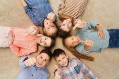 Enfants heureux montrant des pouces sur le plancher Image stock