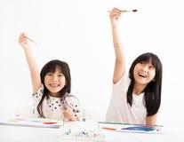 Enfants heureux peignant dans la salle de classe Photographie stock libre de droits