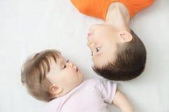 Enfants heureux, portrait de garçon et bébé regardant l'un l'autre, bonheur dans l'enfance des enfants de mêmes parents, mensonge Photo stock